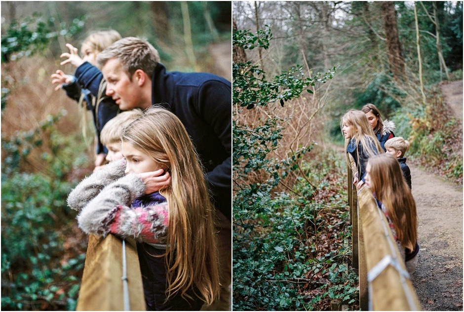 Family leaning on fence looking at view during a natural family winter shoot.