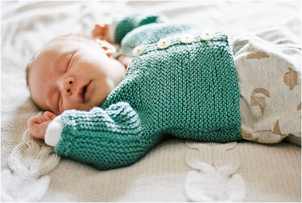 Newborn baby sleeping in knitted, handmade clothes, Hertfordshire.
