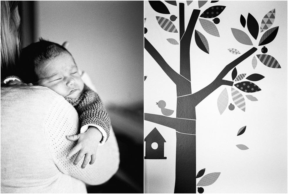 Black and white newborn image of mum holding baby in nursery