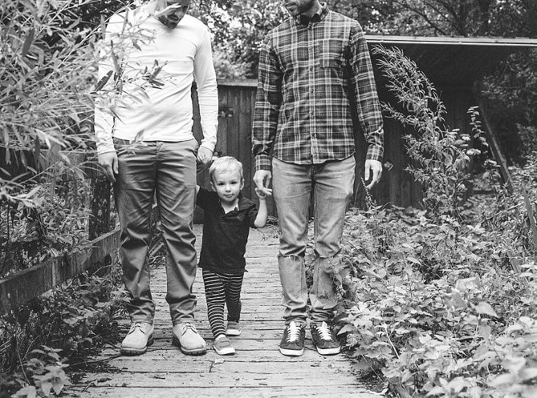 Black and white picture of child holding hands with adults in the woods | Family Woodland Shoot