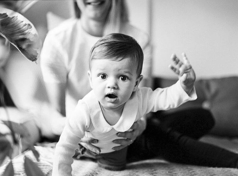 black and white photography of baby looking into camera crawling on sofa