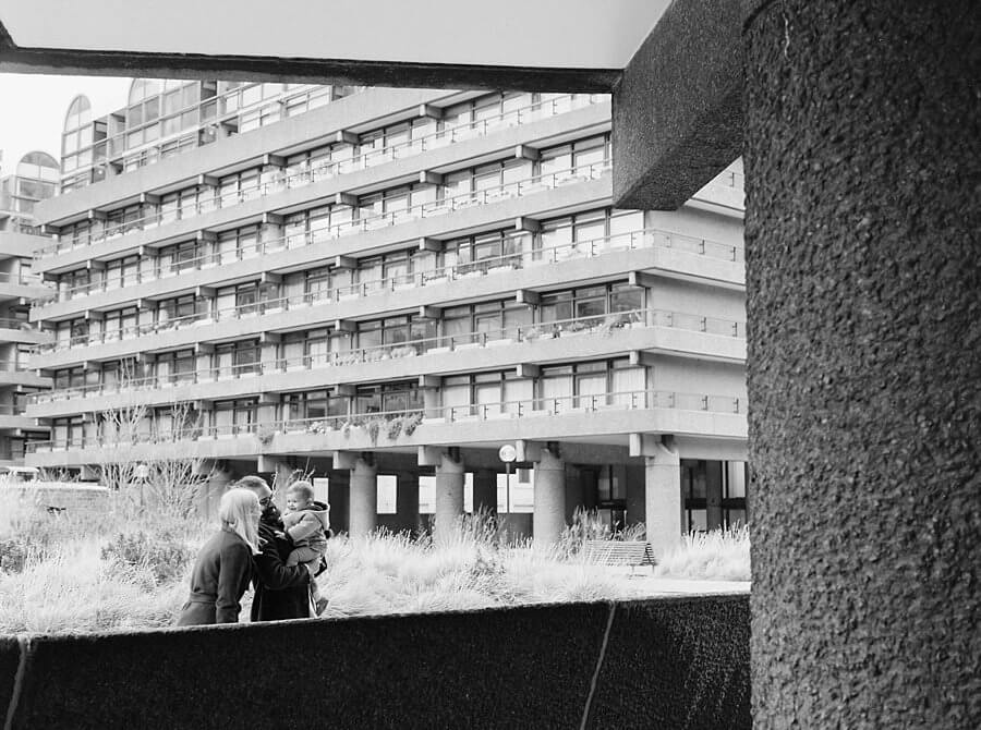 Black and white image of family framed by brutalist building architecture